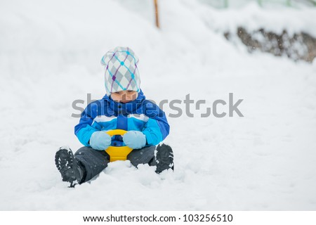 Cute little boy in blue riding on a sled near  the Austrian cottage