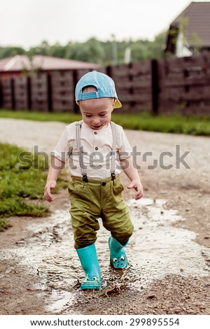 Cute little boy in cap and green rubber boots is having fun splashing through the puddles on the rural road. Image with selective focus - stock photo