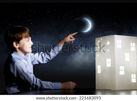 Cute little boy in dark room dreaming about home and family