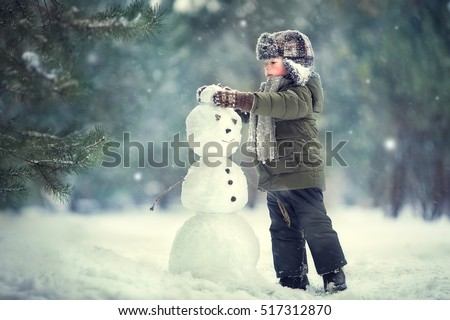 Cute little boy in earflaps hat is making a snowman. Image with selective focus and toning
