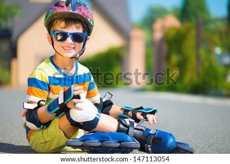 Cute little boy in helmet posing with rollers - stock photo