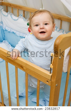 Cute little boy in his crib smiling - stock photo