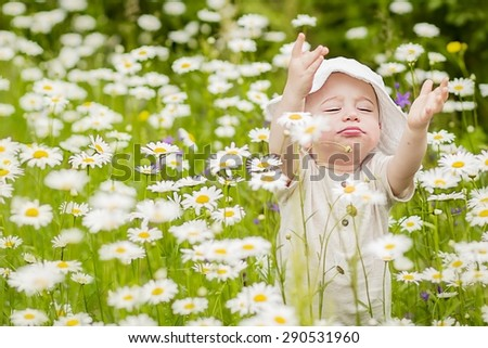 Cute little boy in panama hat in the lawn with camomiles pulling his hands up asking to pick him up in one's arms - stock photo