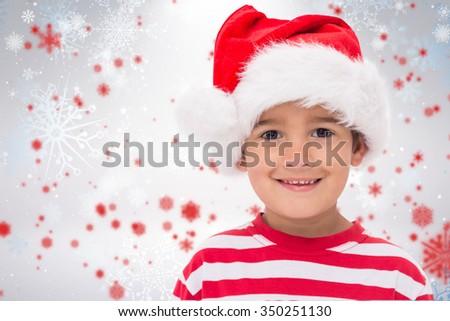 Cute little boy in santa hat against snowflake pattern - stock photo