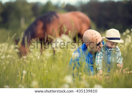 Cute little boy in straw hat and his bald handsome father are examining different herbages growing on the field with a grazing horse on a background. Image with selective focus and toning - stock photo