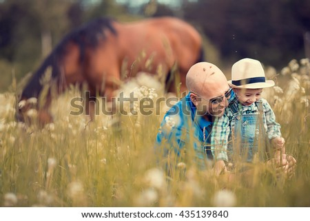 Cute little boy in straw hat and his bald handsome father are laughing examining different herbages growing on the field with a grazing horse on a background. Image with selective focus and toning - stock photo