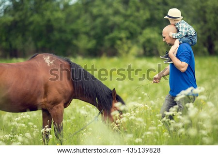 Cute little boy in straw hat sitting on his father's neck trying to feed a grazing horse. Image with selective focus and toning - stock photo