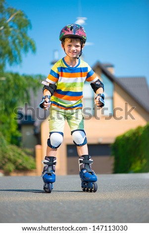 Cute little boy in sunglasses with rollers - stock photo