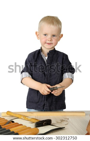Cute little boy in work costume tries to use carpenter tools near the table isolated on white background