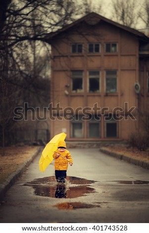 Cute little boy in yellow raincoat with yellow umbrella is walking on the puddles in old park. Image with selective focus and toning - stock photo