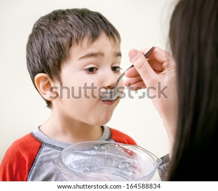 Cute little boy is being fed using spoon - stock photo
