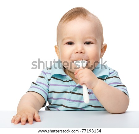 Cute little boy is biting a spoon while sitting at table, isolated over white - stock photo