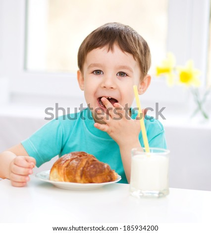 Cute little boy is dipping his tongue in the glass of milk - stock photo