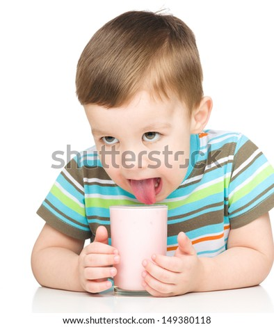 Cute little boy is dipping his tongue in the glass of milk, isolated over white