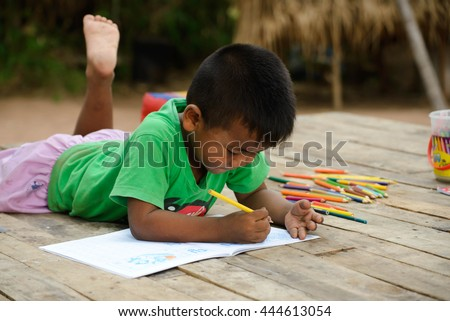 cute little boy is drawing with color pencil at old home - stock photo