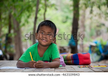 cute little boy is drawing with color pencil at old home