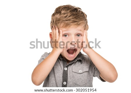 Cute little boy is isolated on white background. Terrified boy screaming, looking at camera and clutching at his head