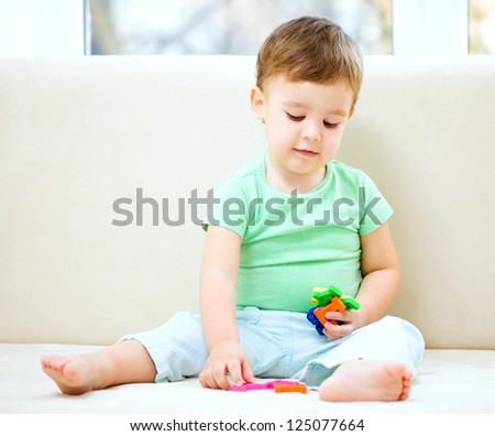 Cute little boy is playing while sitting on couch
