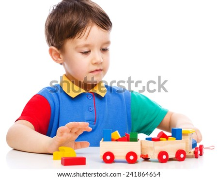 Cute little boy is playing with building blocks, isolated over white - stock photo