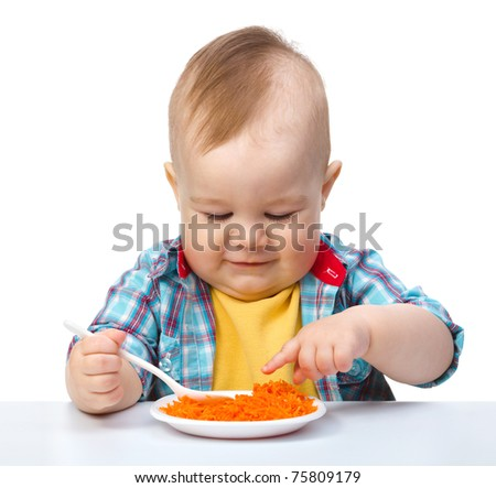 Cute little boy is playing with carrot salad, isolated over white