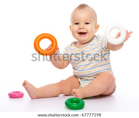 Cute little boy is playing with toys while sitting on floor, isolated over white - stock photo