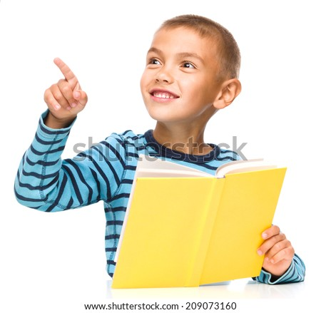 Cute little boy is reading a book while pointing to the left using his index finger, isolated over white - stock photo