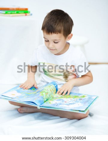 Cute little boy is reading book - stock photo