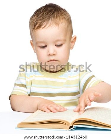 Cute little boy is reading book while sitting at table, isolated over white