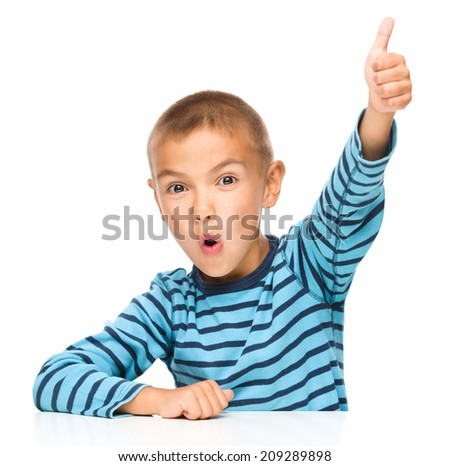 Cute little boy is showing thumb up sign, isolated over white - stock photo