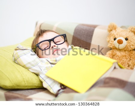 Cute little boy is sleeping in front of his teddy bears wearing glasses and put off a big book - stock photo