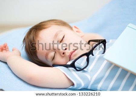 Cute little boy is sleeping while wearing glasses and put off a big book