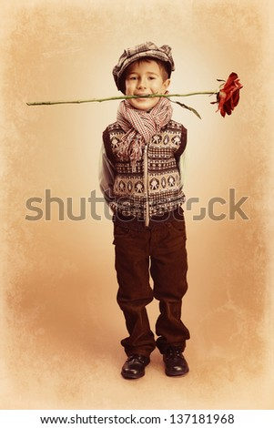 Cute little boy is standing with a red rose in his mouth. Retro style. - stock photo