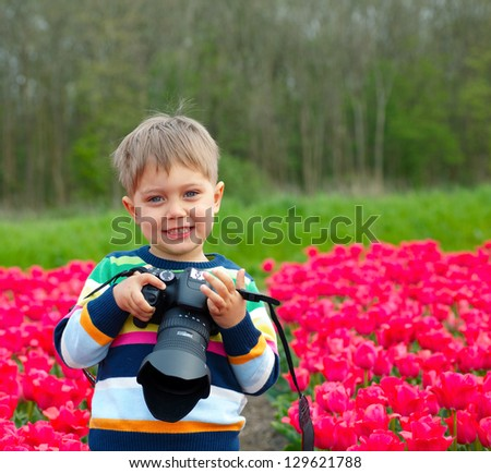 Cute little boy is taking pictures in field with tulips in Holland - stock photo
