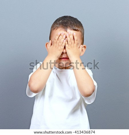 Cute little boy kid covering his face with hands against gray background  - stock photo
