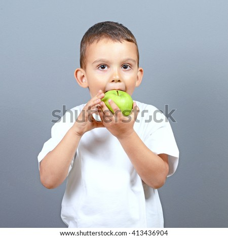Cute little boy kid eating green apple against gray background  - stock photo