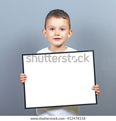 Cute little boy kid holding blank board with space for some text  against gray background  - stock photo