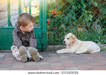 Cute little boy kneeling with his puppy labrador smiling at camera. - stock photo