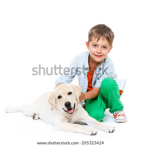 Cute little boy kneeling with his puppy labrador smiling at camera on white background