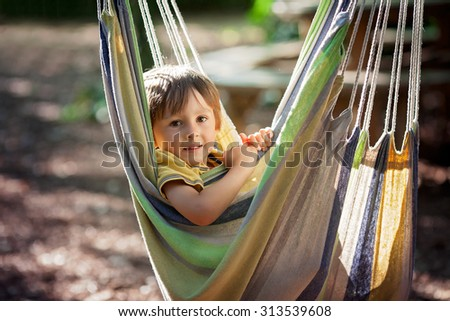 Cute little boy laughing in hammock, child entertaining  - stock photo