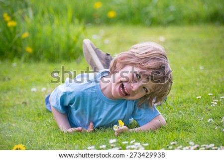 Cute little boy laughing, with daisies in the hand playing  in park in grass on green meadow.  - stock photo