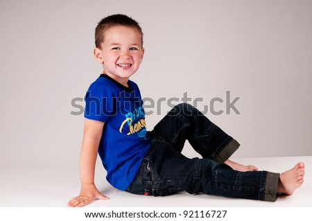 cute little boy laying down in a studio - stock photo