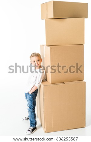 Cute little boy leaning on stack of cardboard boxes  isolated on white