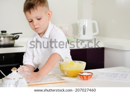 Cute little boy learning to bake cakes carefully putting flour on his board before rolling out his dough - stock photo
