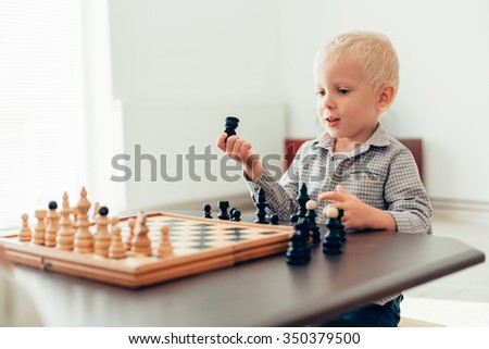 Cute little boy learning to play chess at home - stock photo