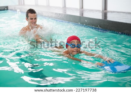 Cute little boy learning to swim with coach at the leisure center - stock photo