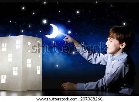 Cute little boy looking at model of house - stock photo