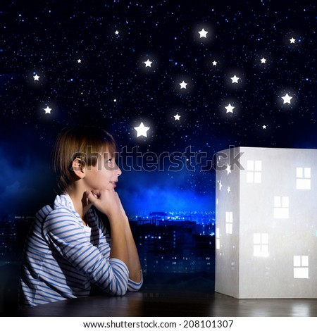 Cute little boy looking at model of house