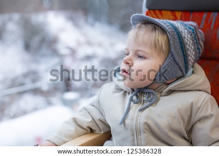 Cute little boy looking out train window outside, while it moving. travel - stock photo
