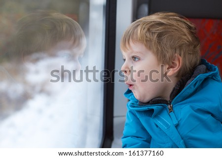 Cute little boy looking out train window outside, while it moving. travel