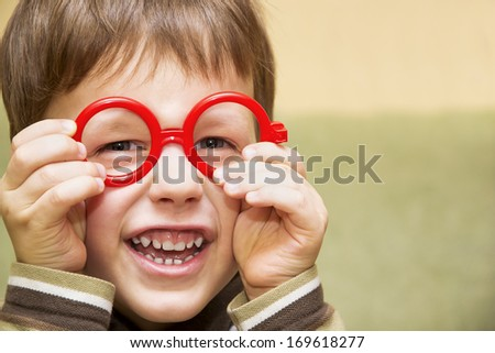 Cute little boy looking through toy red glasses